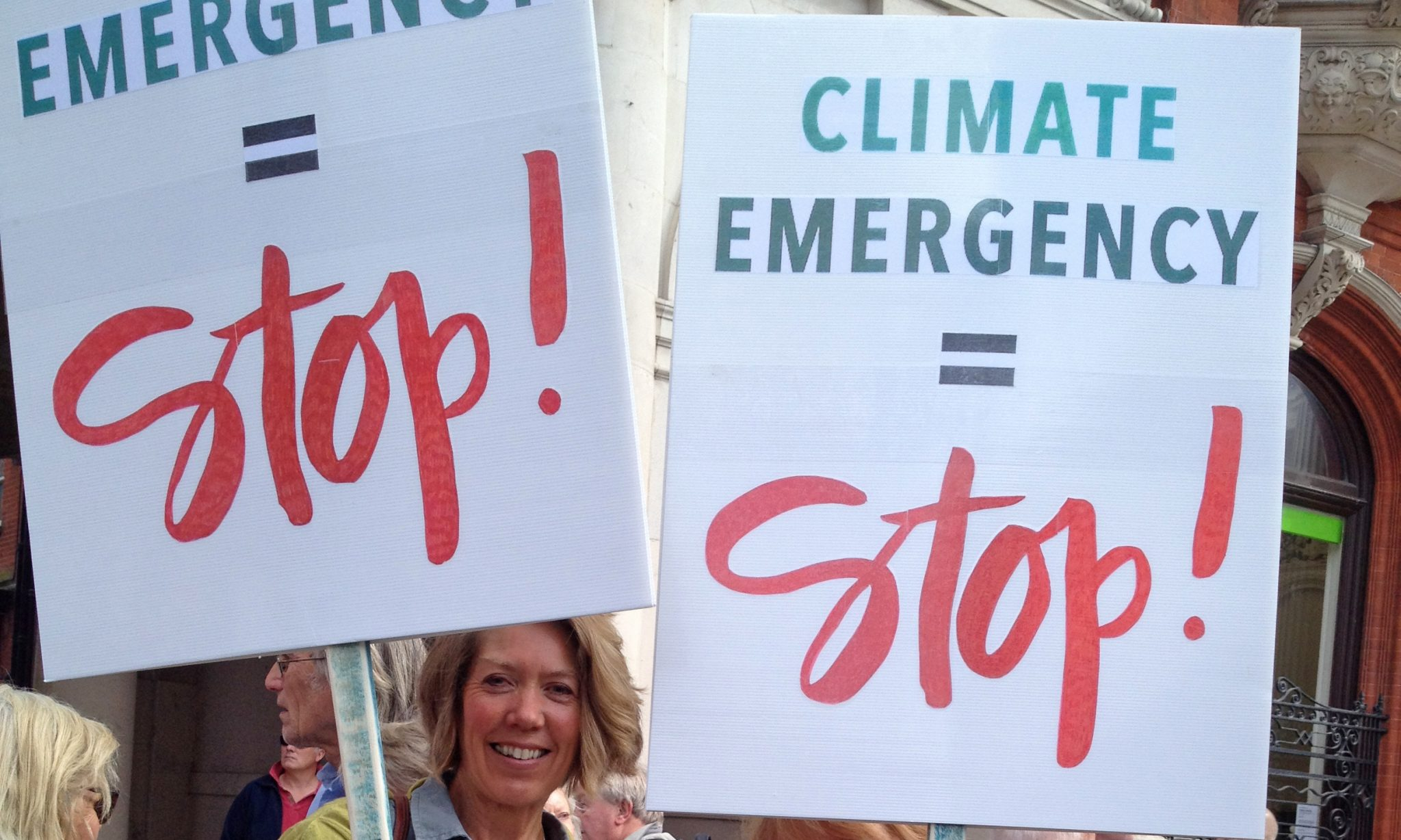 "Woman at demonstration holding placard saying ""CLIMATE EMERGENCY = Stop!"""